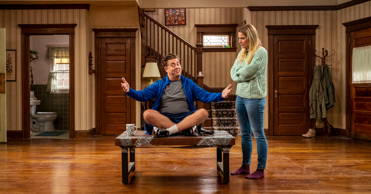 i due protagonisti della serie: lui seduto a gambe incrociate su un tavolo del soggiorno, lei che lo guarda perplessa - nerdface
