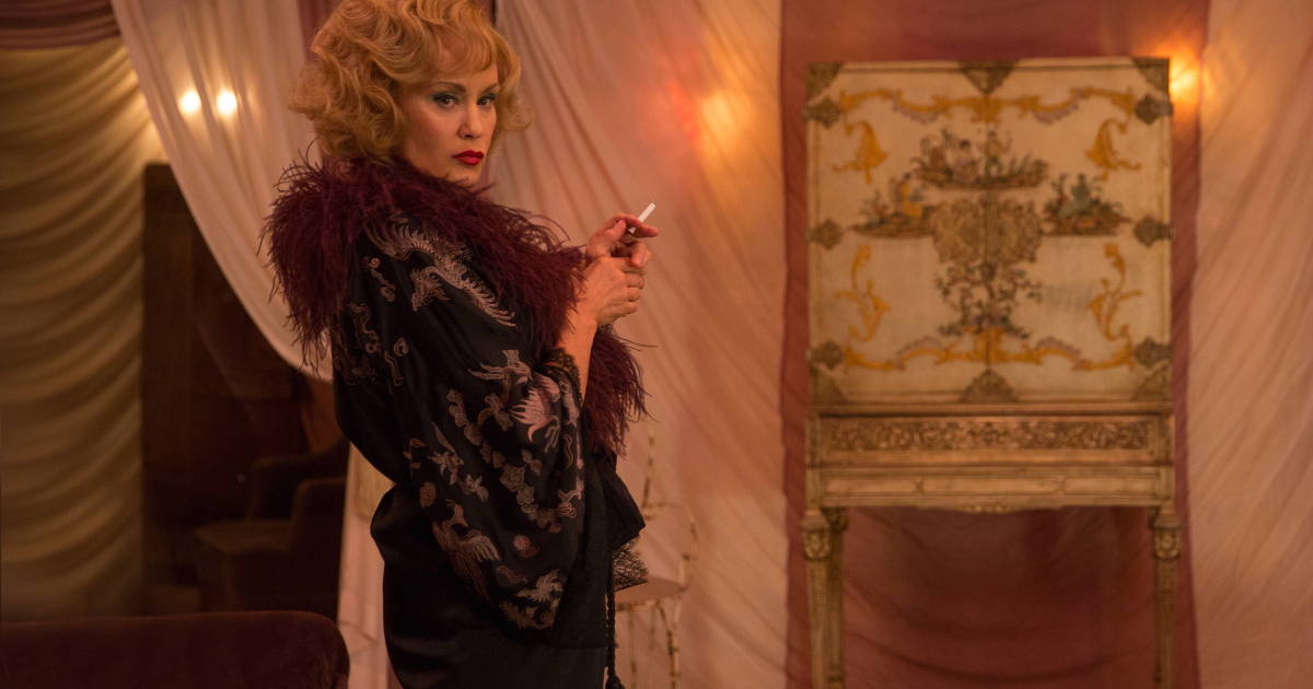 una donna vestitas in nero guarda avanti a sé mentre tiene una sigaretta - nerdface
