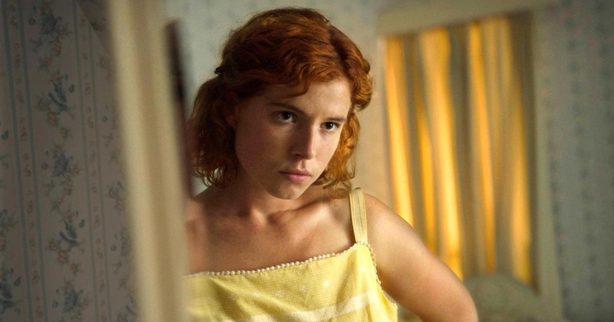 l'attrice protagonista è in una stanza ed è poggiata sullo stipite della porta, indossando una canottiera gialla - nerdface