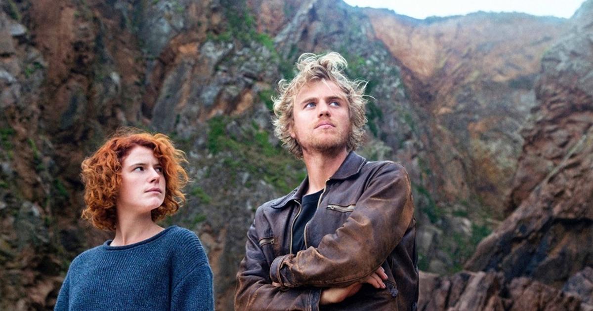 i due protagonisti di beast sono davanti alcuni monti, lei guarda lui - nerdface