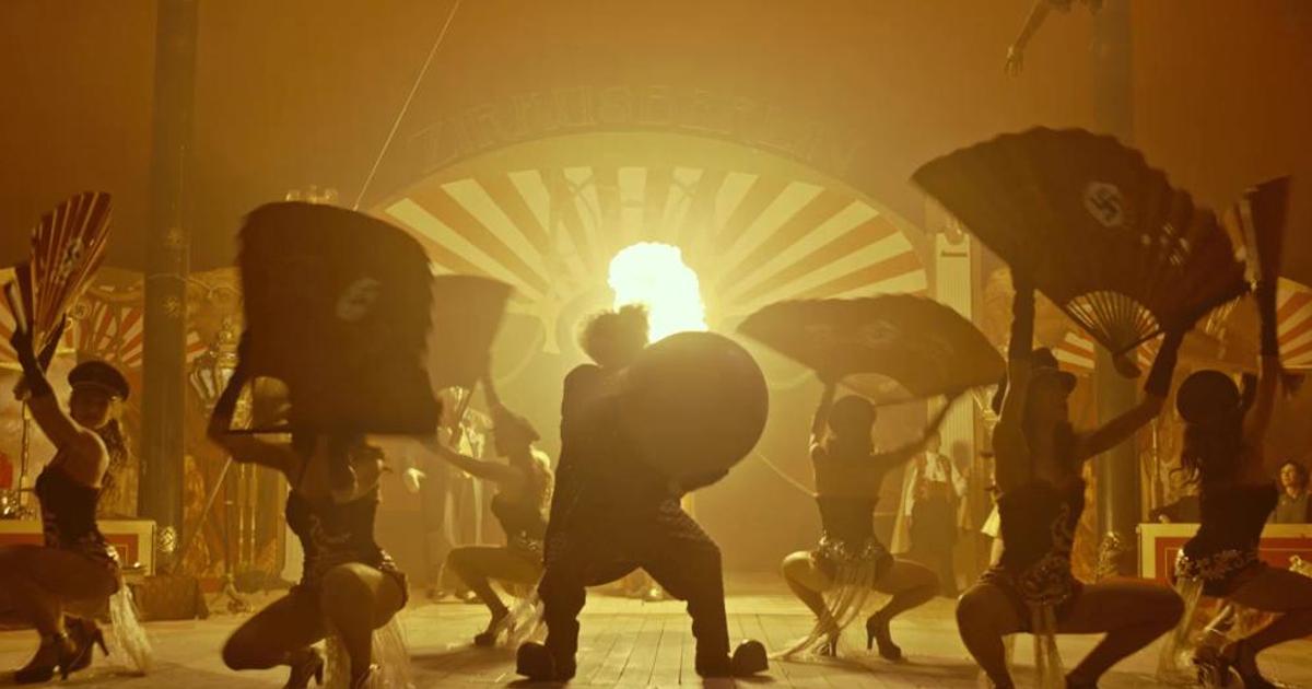 uno spettacolo del circo con donnine e ventagli finisce sotto una luce arancione - nerdface