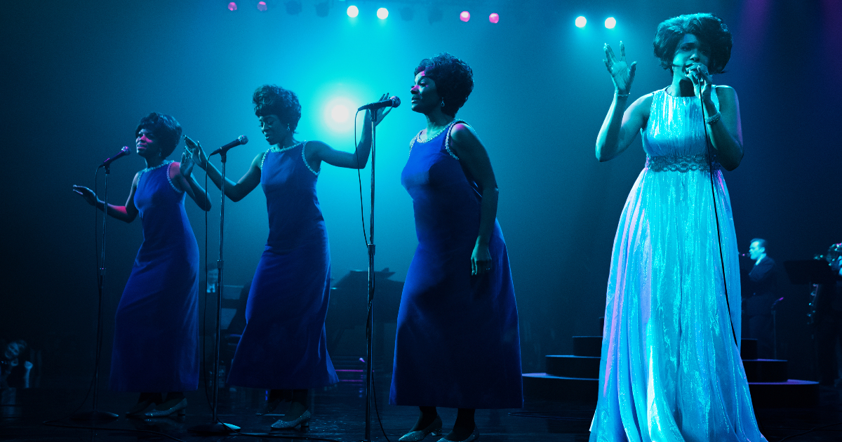 vestita di bianco e su palco illuminato di blu, aretha canta accanto a tre coriste - nerdface
