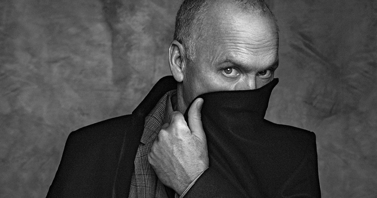 un curioso ritratto di michael keaton in bianco e nero mentre si copre metà volto col bavero del cappotto - nerdface