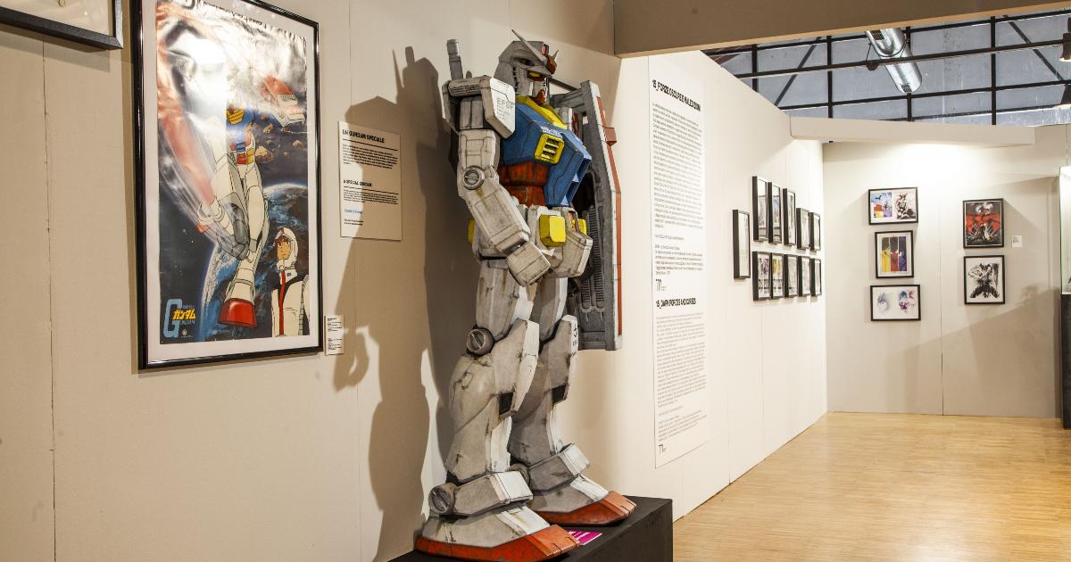 una statua di gundam esposta accanto a un manifesto dell'anime - nerdface