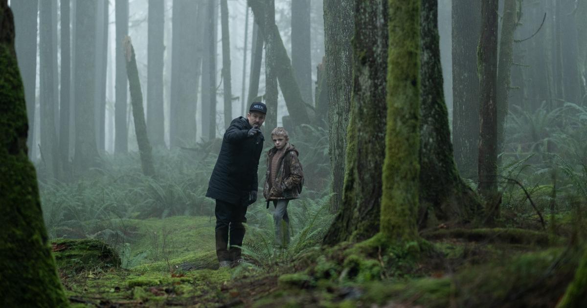 il bambino è nel bosco e un poliziotto indica un punto davanti a lui - nerdface