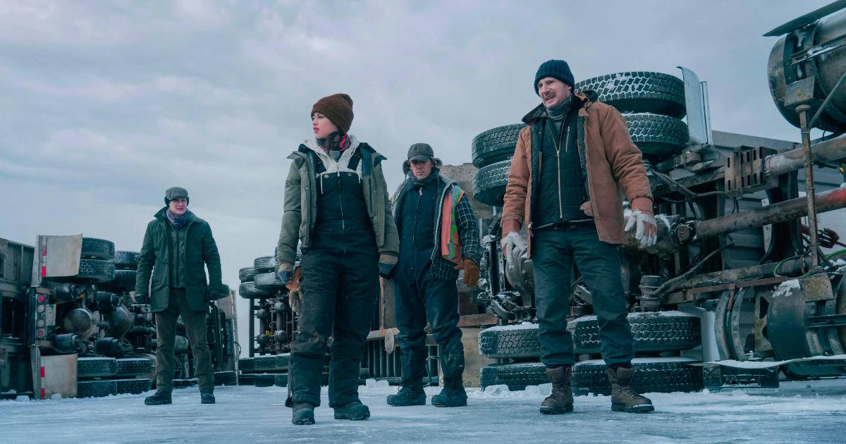 liam neeson e i suoi uomini sono in piedi davanti a due camion rovesciati - nerdface